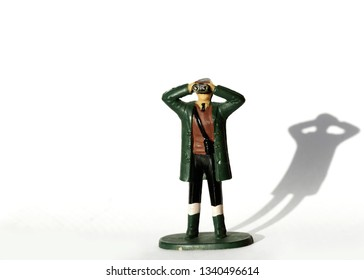 Small miniature toy figure of a man holding up and looking through a pair of binoculars on white background with a shadow