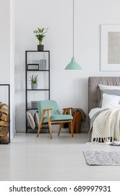 Small mint lampshade hanging above comfy wooden chair in bedroom