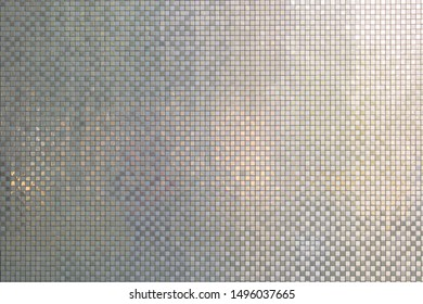 Small mirror tile on an exterior of a building. Glossy facing and cladding.