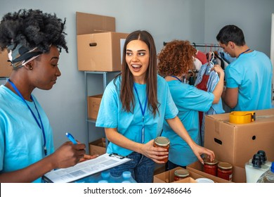 Small mixed race group of people working in charitable foundation. Male and female teenage food bank volunteers sort canned food items in cardboard boxes. Happy volunteer in community food bank