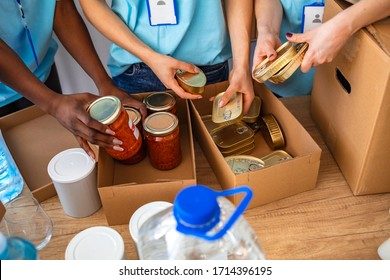 Small mixed race group of people working in charitable foundation. Generous people helping to poor people. People Donating Food To Charity Food Bank Collection In Community Center