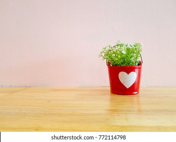small mock up or fake plant in the red pot with white heart sign on the wooden table with pink wall background.