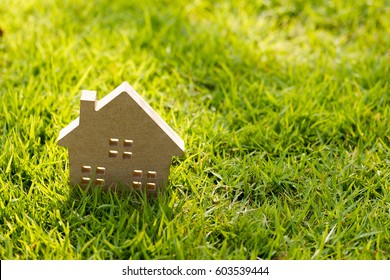 Small model of house over green grass dueling sunlight.