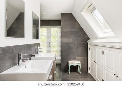 Kleines modernes Badezimmer mit Doppelwaschbecken und dunklen Fliesen