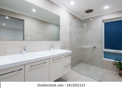 Small modern bathroom interior with light color tiling, double vanity, and glass shower screen. PERTH, AUSTRALIA. MAY 2019.