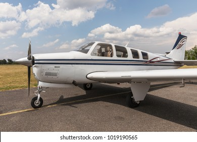 Small modern business or personal airplane for fast transportation on runway in sunny day.