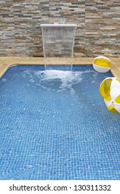 Small modern swimming pool with artificial waterfall