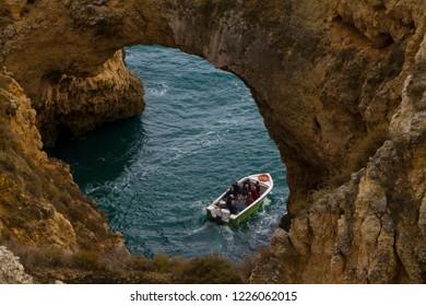 Small motor boat with several people heading through a natural stone arch in farol da ponta da piedade the algarve portugal on a wonderful sunny day