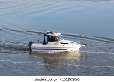 Small motor boat slowly moving on water