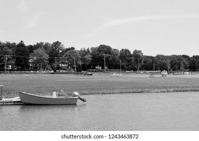 A small motorboat moored in Bluefish River Reservoir with other boats in the background, Duxbury, MA.