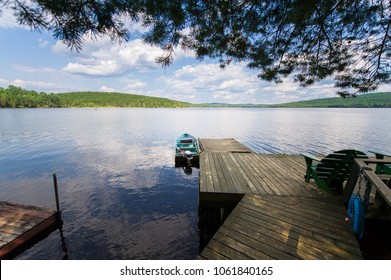 Small motorboat tied to a wooden dock. On the dock there's a Adirondack chair