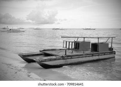 A small motorized boat waits for its passengers in the shore. The sky is clear with some clouds but generally the weather is good for snorkeling and diving. Photo in black and white.