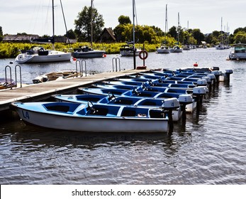 Small motorized dinghies for hire; moored to wooden jetty