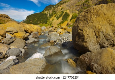 Small mountain brook with flying water with big stones , long exposition