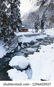 A small mountain river Amanauz flows over the rocks of the winter Dombay valley. Cloudy snow day in the resort village