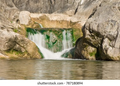 Small mountain waterfall on the rocks covered with moss deep in the forest. Cliffs in Cheile Turzii, Romania. Autumn is coming. Beautiful, calming nature background