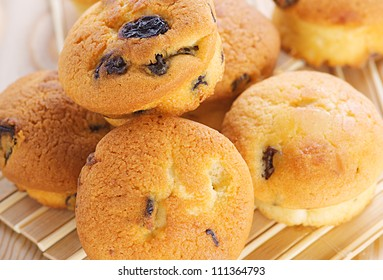 Small muffins with raisins on bamboo table cloth.