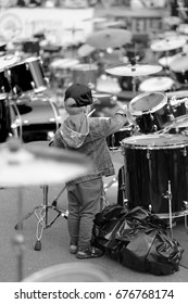 A small musician, participant of a concert of percussion music, behind a drum set.