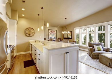 Small narrow kitchen area with white cabinets and pendant lights. View of dining room.