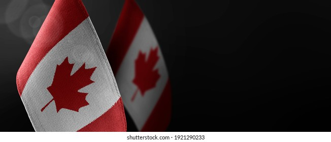 Small national flags of the Canada on a dark background