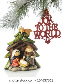 """A small nativity scene under the branches of a Christmas tree with an ornament saying, """"Joy to the World"""" hanging nearby.  On a white background."""