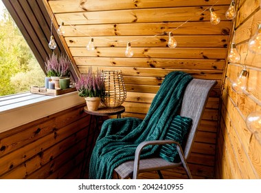Small natural color wooden cabin balcony with heather flowers, candlelight flame, soft dark green plaid waiting on garden furniture chair. Cute autumn hygge home decor arrangement.