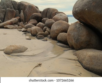 small natural stone wall with rounded shape creating a natural protection the waves, beach De Cima, Pinheira, SC, brazil