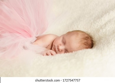 A small newborn girl is lying on a white blanket in a full pink tutu skirt made of tulle. Aerial dreams