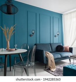 Small and nice designed living room with couch and dining area and stylish blue wall with molding