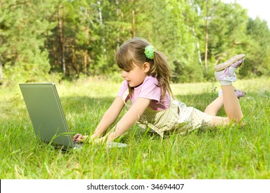 The small nice girl works on a computer, lays on a beautiful green lawn, Smile .