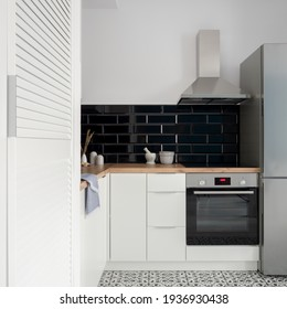 Small and nice kitchen with white cupboards, drawers and wardrobe, black wall tiles, wooden countertop and silver kitchen appliances