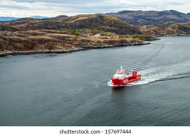 Small Norwegian red oil products tanker ship sails in fjord