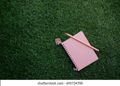 Small notepad and pencil on grass background and copy space