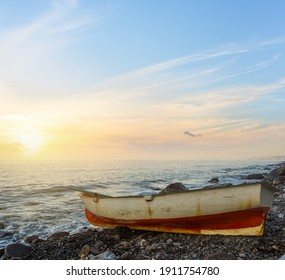 small oar boat on sea coast at the sunset, natural travel background