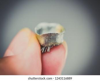 Small object printed on metal 3d printer macro. Dental crowns created in laser sintering machine close-up. SLM, SLS technology. Concept 4.0 industrial revolution. Progressive modern additive technolog