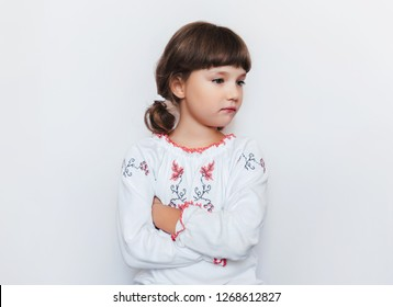 A small offended girl stands with arms crossed. Children's protest. White background. Copy space. Ukraine is offended by the enemy.