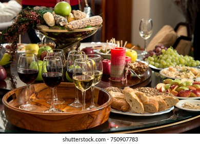 A small official reception. On the table, apples, nuts, candied fruits and glasses with red and white wine.