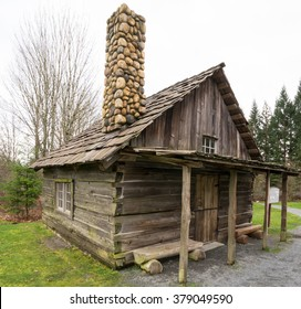 Small old log cabin in a large meadow