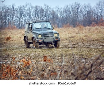 Small old offroad car going through mud in a forest
