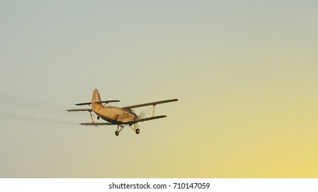 small old plane for agricultural spraying, flying in the sunset sky