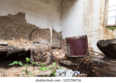 Small, old, rusty metal pot in abandoned house