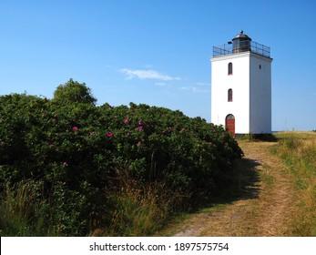 Small old traditional lighthouse landmark and toursit attraction on the coast Baagoe Bågø Island Funen Denmark
