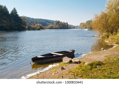 small old wooden fishing boat (punt) on the bank of a river, bright sunny day, forest in background
