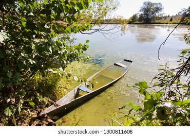 small old wooden fishing boat (punt) on the bank of a lake, bright sunny day