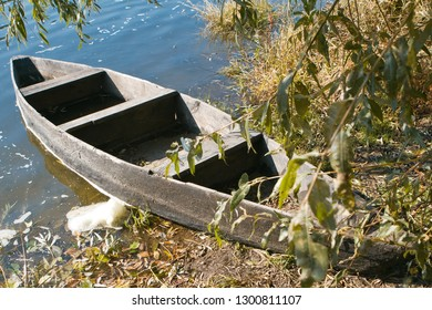 small old wooden tar covered boat (punt) on the bank of a river, bright sunny day