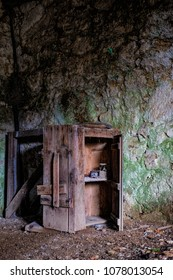 Small old wooden wardrobe against stone wall