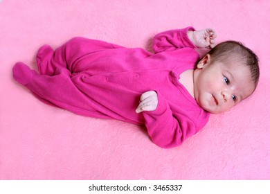 small one week old newborn baby on a pink background
