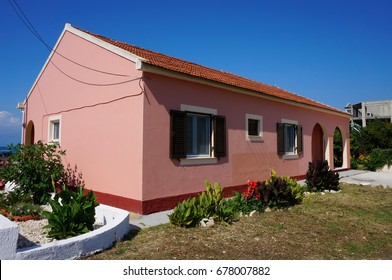 A small one-story house, painted with pink paint, on the island of Corfu, Greece