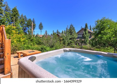 Small but open to greenery back yard space with fire and hot tub and wooden deck