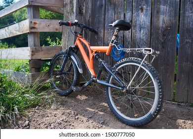 Small orange bicycle with full suspension parked in a village